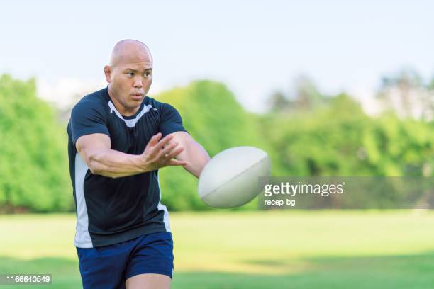 rugby player passing ball to team-mate - passing sport stock pictures, royalty-free photos & images