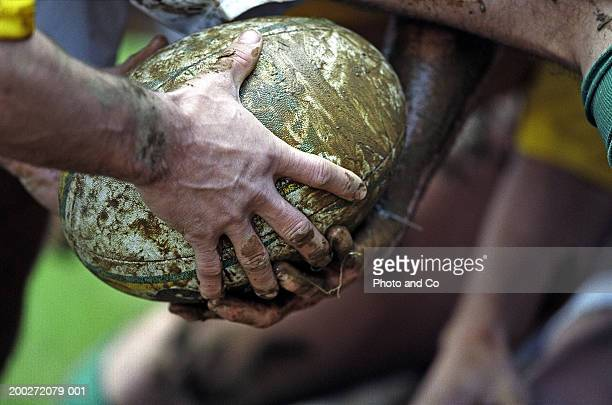 Rugby player passing muddy ball through legs, close-up