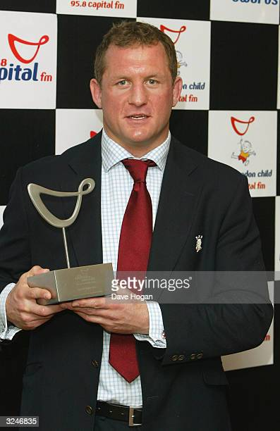 """Rugby player Richard Hill on behalf of the England Rugby team, with the award for London's favourite sporting team in the awards room at the """"Capital..."""