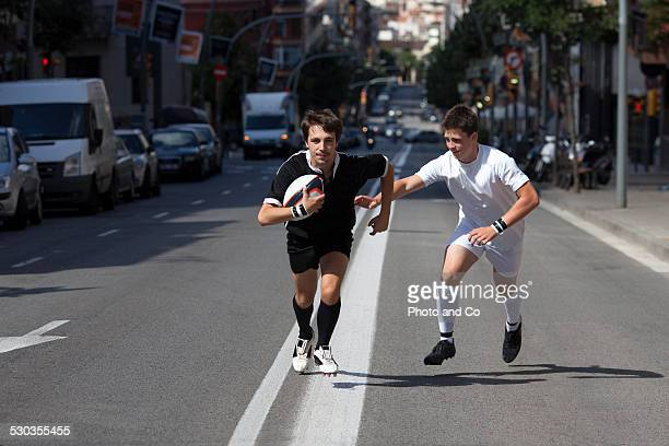 Rugby player running with ball, player chasing