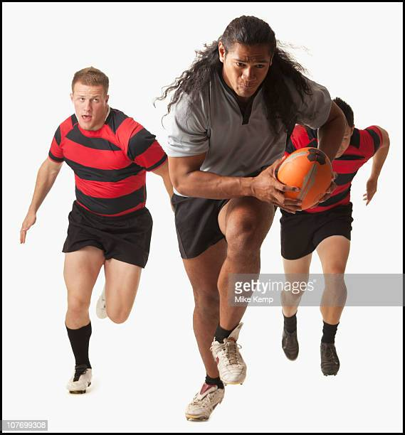 Rugby player running with ball, team chasing