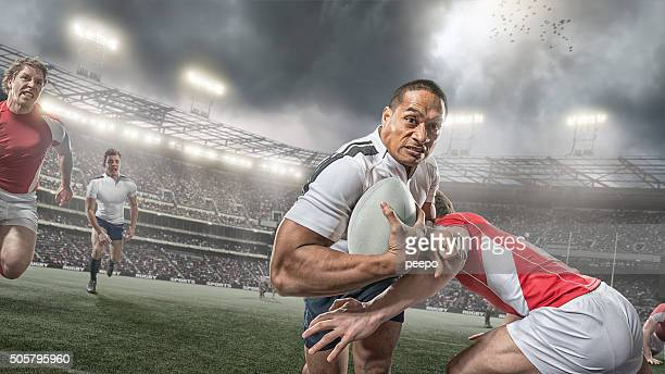rugby player running with ball whilst being tackled during game - rugby stock pictures, royalty-free photos & images