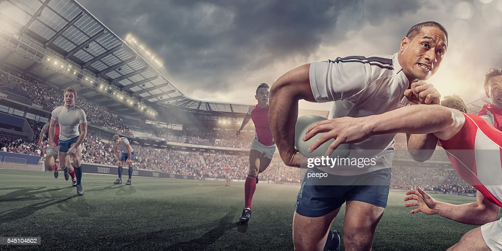 Rugby Player Running With Ball Whilst Being Tackled During Match : Stock Photo