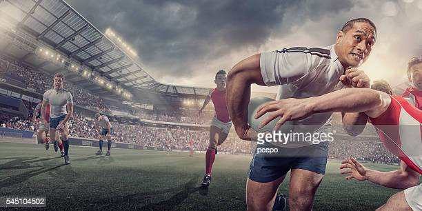 rugby player running with ball whilst being tackled during match - rugby stock pictures, royalty-free photos & images