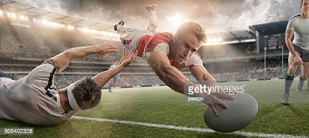 rugby player scoring and being tackled in mid air dive - rugby stock pictures, royalty-free photos & images