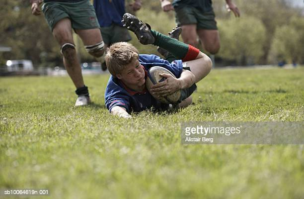 Rugby player scoring falling on groud with ball, surface view