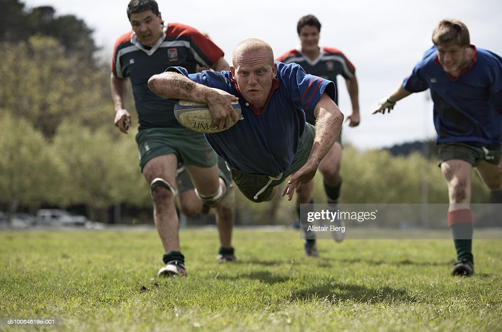 Rugby player scoring jumping on groud with ball : Stock Photo