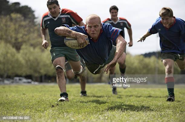 rugby player scoring jumping on groud with ball - rugby stock-fotos und bilder