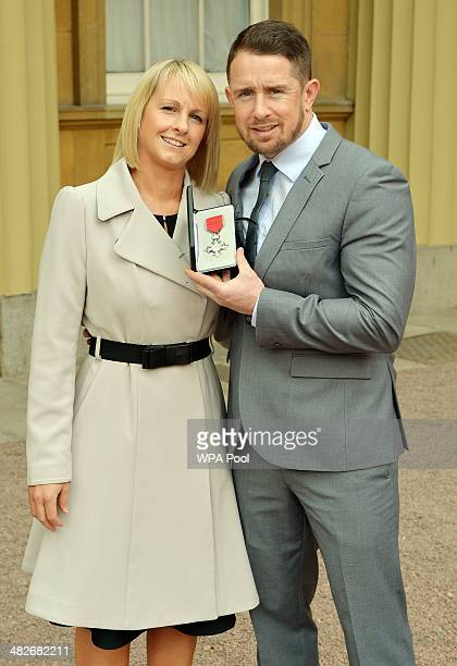 Rugby player Shane Williams poses with his wife Gail as he holds his MBE after it was presented to him by Prince Charles Prince of Wales during an...