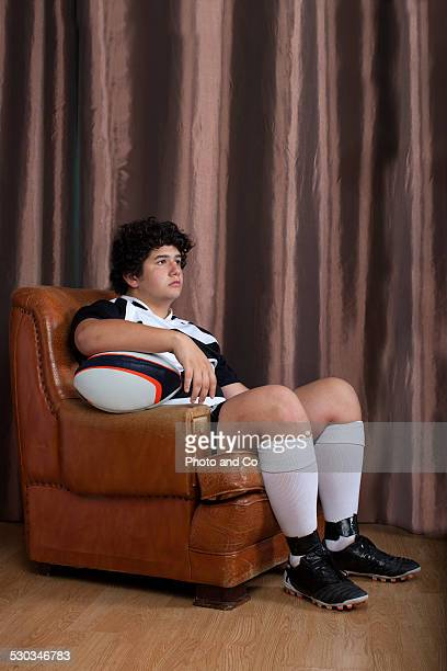 rugby player sitting in a club chair - assis ストックフォトと画像
