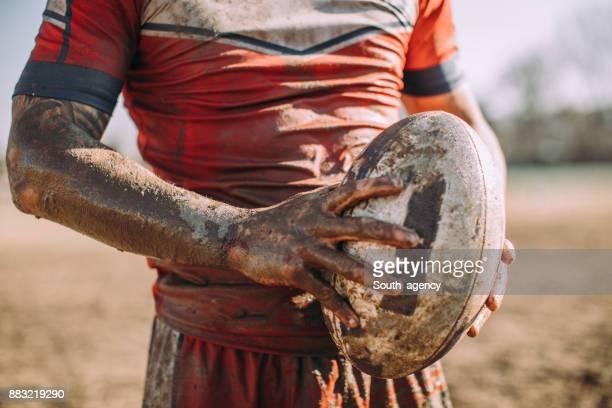 rugby-spieler stehen auf einem spielfeld mit ball - trikot stock-fotos und bilder