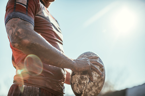 Rugby player standing on a playing field with ball 924250222