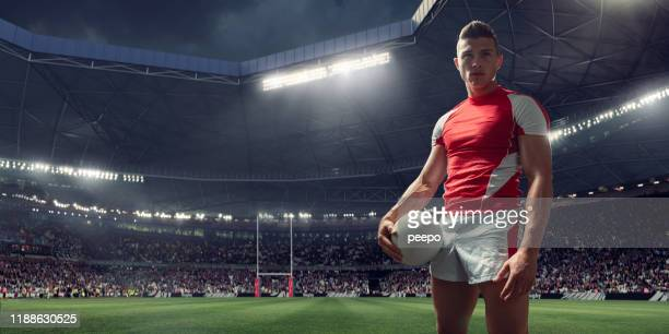 rugby player standing with ball in floodlit stadium before match - stadium stock pictures, royalty-free photos & images