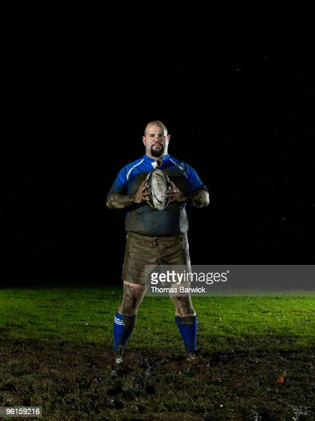 rugby player standing with ball on muddy field - rugby sport photos et images de collection