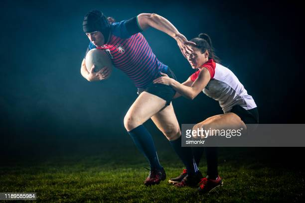 rugby player tackling her opponent - tackling stock pictures, royalty-free photos & images