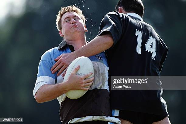 rugby player tackling opponent in possession of ball - タックル ストックフォトと画像