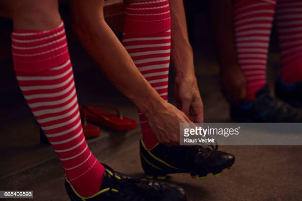 rugby player tying shoe in changing room - rugby players in changing room stock photos and pictures
