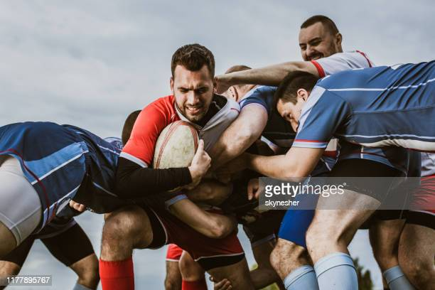 rugby players blocking their opponent on a match at playing field. - rugby union stock pictures, royalty-free photos & images