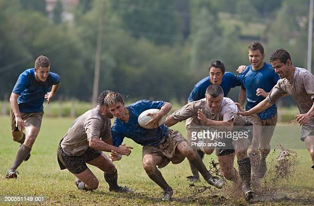 rugby players covered with mud, tackling opponent - rugby stock-fotos und bilder