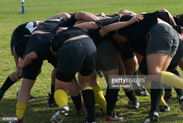 Rugby players forming scrum in a field