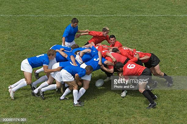 rugby players forming scrum on field, elevated view - scrum stock pictures, royalty-free photos & images