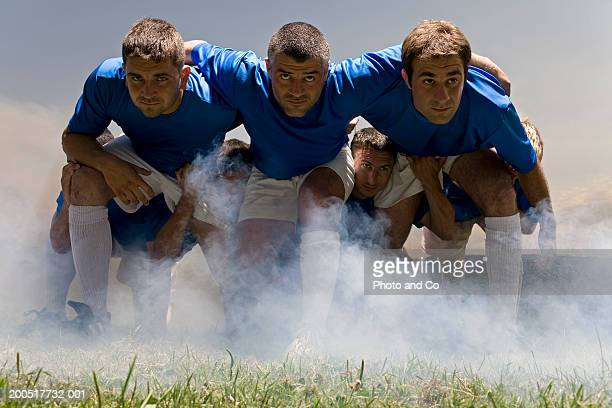 Rugby players in scrum, ground view
