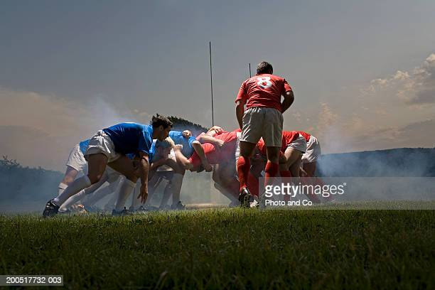 rugby players in scrum on pitch, ground view - rugby stock-fotos und bilder