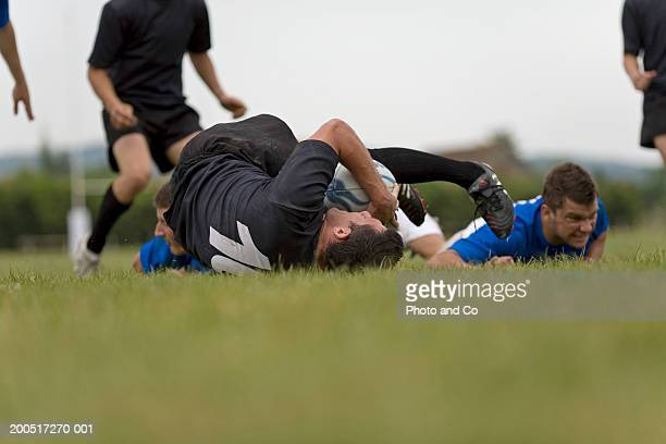 Rugby players in tackle on pitch, ground view