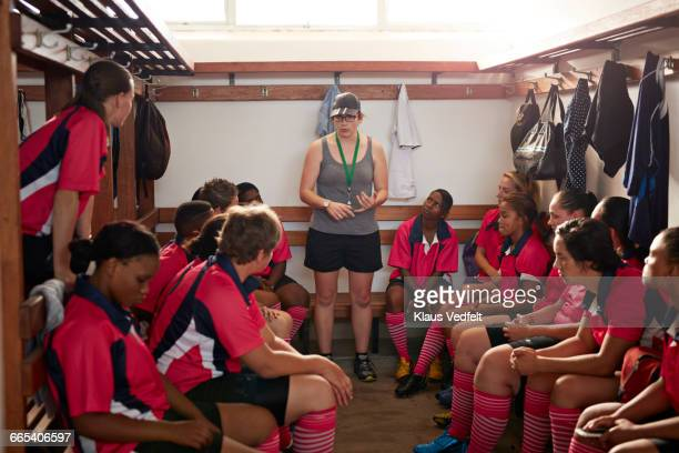 Rugby players listening to coach in changing room