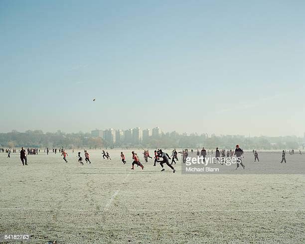 rugby players running after ball in cold landscape