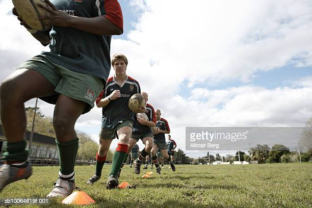 Rugby players running around plastic cones, low angle view