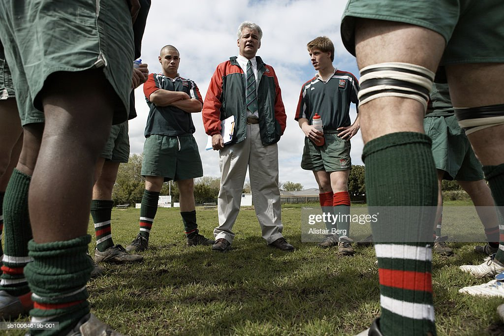 Rugby players standing around coach on lawn, low angle view : Stock Photo