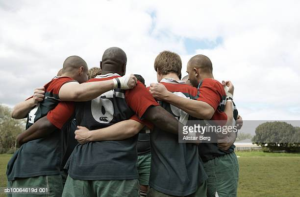 rugby players standing in circle on football field, rear view - rugby team stock pictures, royalty-free photos & images