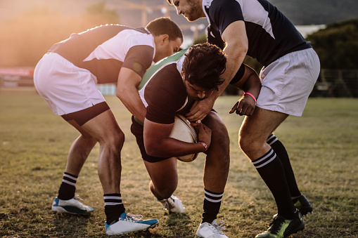 Rugby players striving to get to the ball 1095014886