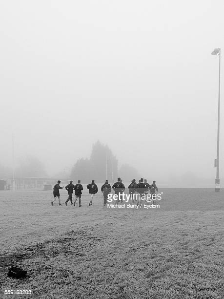 rugby players warming up together against clear sky during foggy weather - rugby team stock pictures, royalty-free photos & images