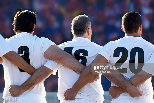 rugby team standing with arms locked, rear view - rugby union photos et images de collection