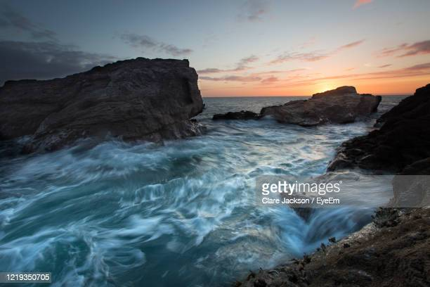 a rugged cornish coastal landscape with crashing waves at sunset with motion blur and dramatic skies - rock stock pictures, royalty-free photos & images