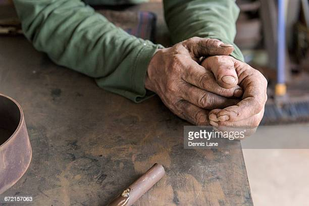 rugged hands of artist leaning on table in workshop - ruffled stock pictures, royalty-free photos & images