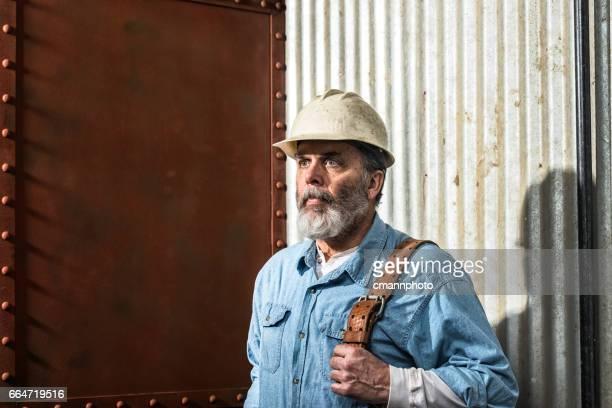 Robuust ogende middelbare leeftijd bouwvakker op bouwterrein