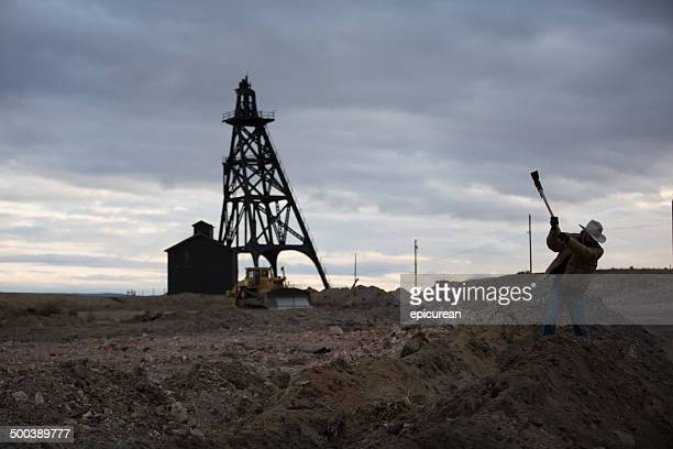 Rugged man swings pickaxe in front of old oil drill