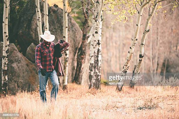 Rugged man walks through woods carrying blanket and looking down