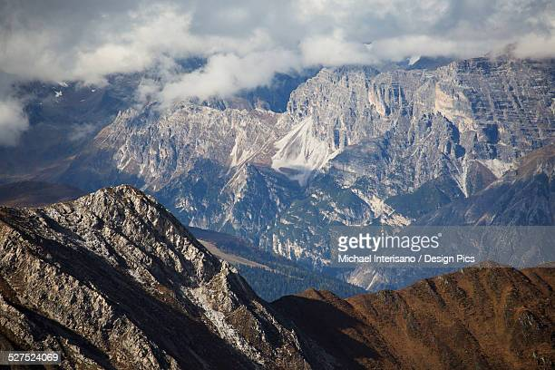 Rugged mountain peak with sun lit mountain range in the distance with cloud covering the peaks