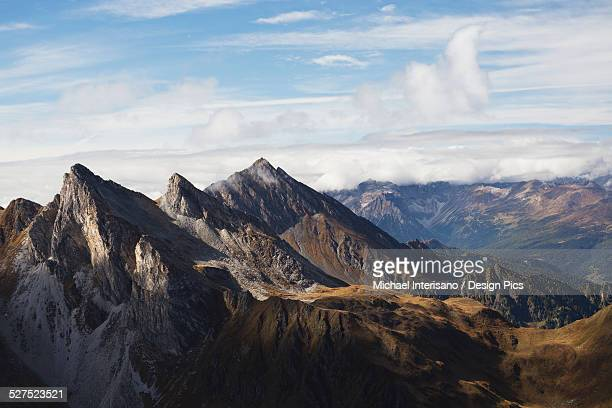 Rugged mountain peaks with clouds and blue sky