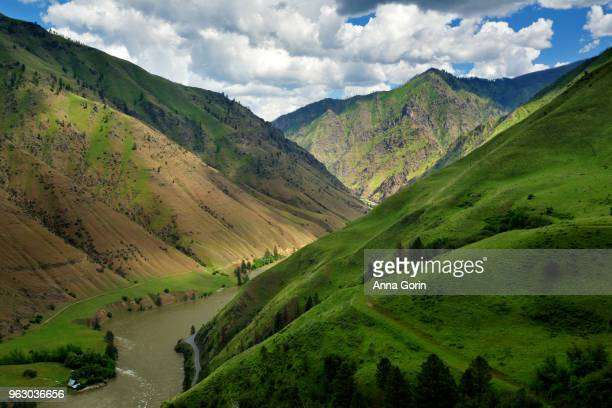 Rugged mountains and lush green hills rising up steeply from banks of Salmon River outside Riggins, Idaho, in spring