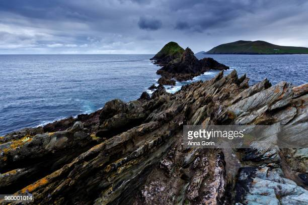 Rugged rock formations jutting into ocean at Slea Head on Dingle Peninsula with Blasket Islands on horizon
