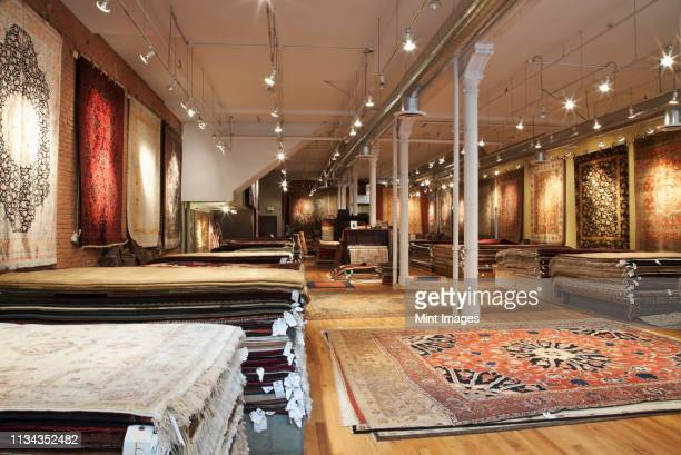 rugs on display in shop - persian rug stock pictures, royalty-free photos & images