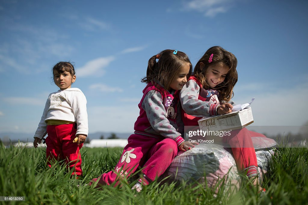 Ruhiv, 2, Inas, 7 and Kulistan, 8, from Al-Hasakah in Syria relax in a field near a refugee camp at the Greek-Macedonia border on March 06, 2016 in Idomeni, Greece. Doctors are warning that conditions at the camp are becoming dangerous for children, with medics dealing with a range of illnesses, including hypothermia. The transit camp at the border is becoming increasingly overcrowded as thousands of refugees continue to arrive from Athens and the Greek Islands. Macedonia's border with Greece remains 'open' but after allowing 580 refugees a day to cross into the country at the beginning of the week, the numbers passing have fallen dramatically with only a handful every day. According to local authorities approximately 12,000 refugees and migrants now remain stuck at the border as they wait to enter Macedonia to continue their journey North into Western Europe.