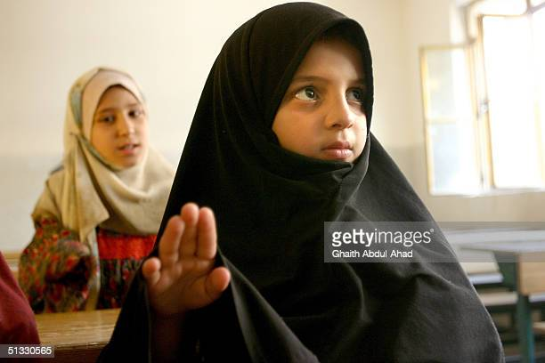 Ruhiya Ali a teacher in in the Jana Madrassa a koranic school for girls reads from a book in the Shiite slums of Sadr city September 9 2004 in...