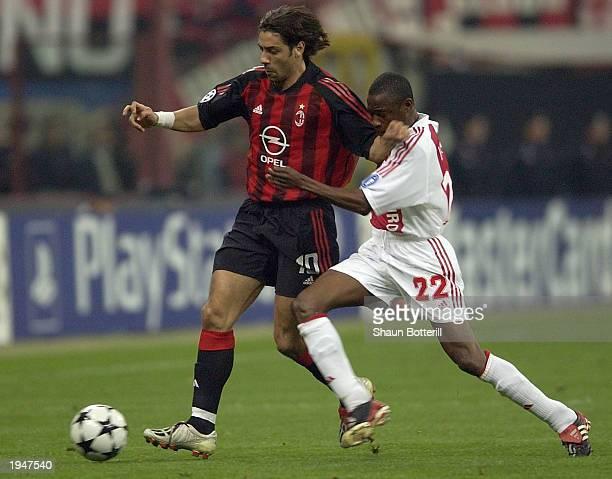 Rui Costa of AC Milan is challenged by Abubakari Yakubu of Ajax during the AC Milan v Ajax quarter final 2nd leg Champions League match on April 23...