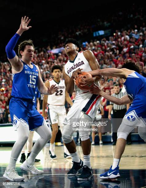 Rui Hachimura of the Gonzaga Bulldogs battles for possession of the ball against Elijah Bryant of the BYU Cougars while BYU's Payton Dastrup looks on...